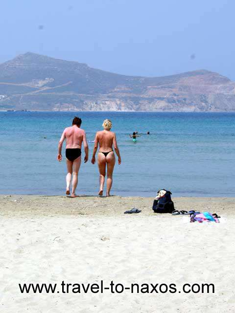 COUPLE SWIMMING - A couple entering the sea at Agios Georgios beach